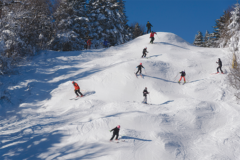 group of ski students skiing moguls