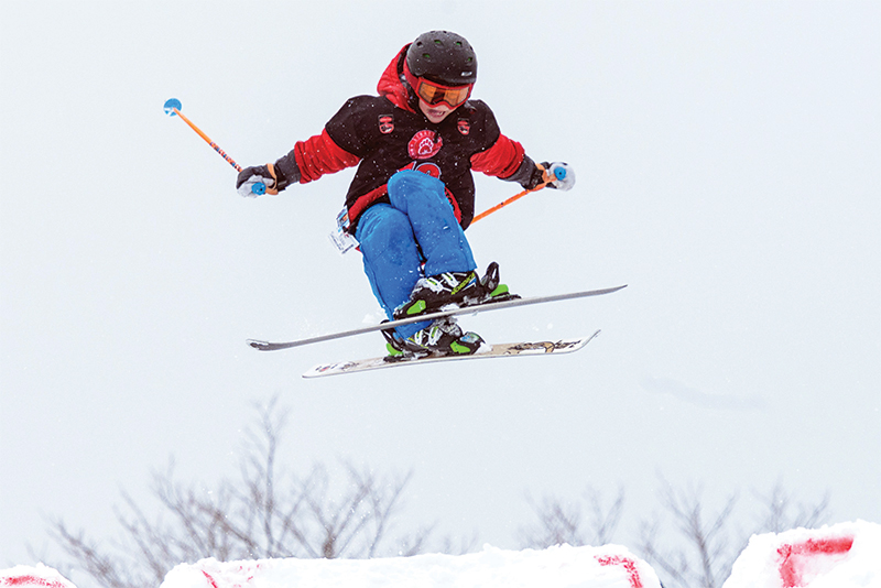 young boy on skis going off a jump
