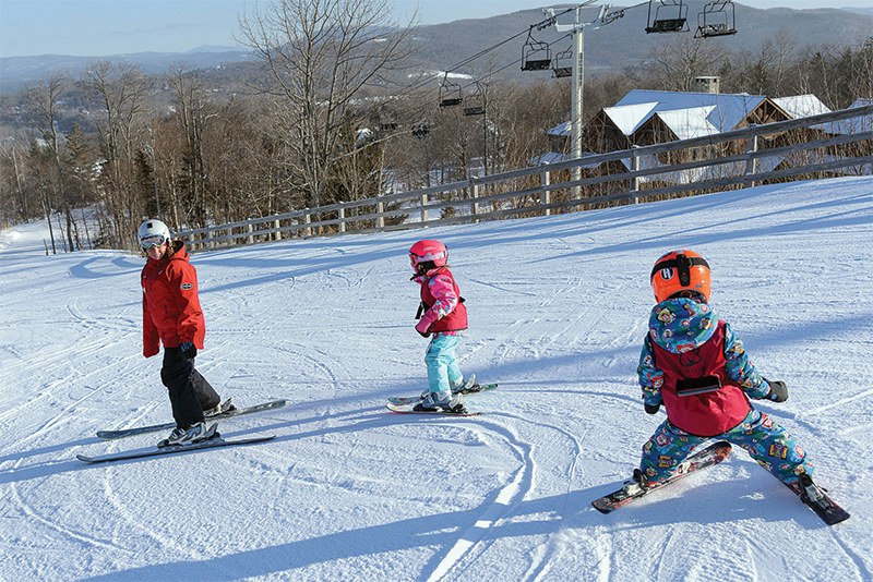 instructor teaching small kids to ski