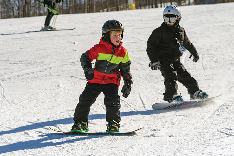young boy riding a snowboard