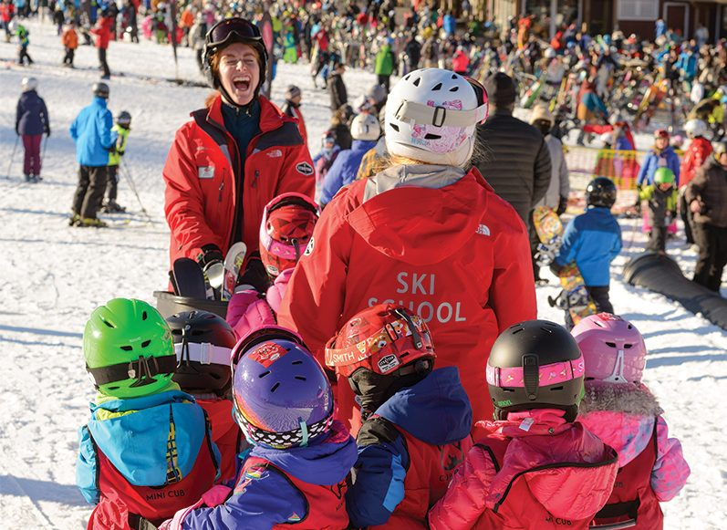 ski instructor laughing and leading a group of kids
