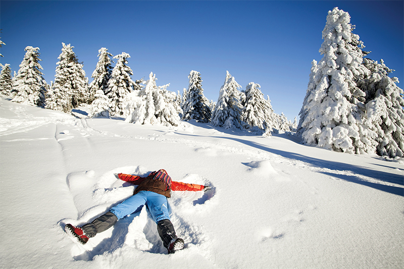 girl making snow angel in snow